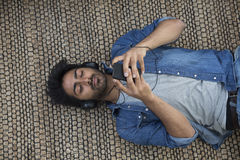 Indian Man lying on floor at home and using smartphone. Royalty Free Stock Photos