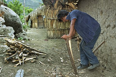 Indian man makes at home firewood small. Guatemala, Chiquimula department, village, municipality Jocotan: in the mountains is huge poverty, why should people Royalty Free Stock Images