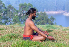 Indian man meditating on green grass Stock Photo