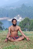 Indian man meditating in lotus yoga pose on green grass. In Kerala, South India Royalty Free Stock Photography