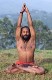 Indian man meditating in lotus yoga pose on green grass in Keral. Healthy life exercise concept - sporty fit Indian man doing breathing exercises in lotus yoga Stock Photo
