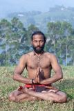 Indian man meditating in lotus yoga pose on green grass in Keral. Healthy life exercise concept - sporty fit Indian man meditating in lotus yoga pose on green Royalty Free Stock Photos