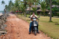 Indian man on motorbike on the road next to the Samudra beach. KOVALAM, INDIA - DEC 28, 2014: Unidentified Indian man on motorbike on the road next to the Royalty Free Stock Photography