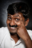 Indian man with moustache. Handsome Indian man with moustache and raise eyebrow smiling and looking at camera close-up stock photography