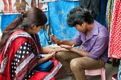 Indian man painting Henna paste on woman's hand at the Russell market in Bangalore Stock Image