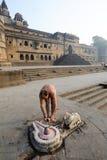 Indian man performs pooja on sacred river Narmada in Maheshwar Royalty Free Stock Photography