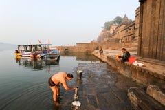 Indian man performs pooja on sacred river Narmada in Maheshwar Royalty Free Stock Image