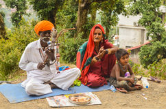Indian Man Playing Musical Instrument on Road. Indian Man from Rajasthan plays string musical instrument with a bow  while his family sings. This is an example Stock Photography