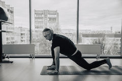 Indian man practicing yoga in doors, european city at background royalty free stock photo