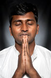 Indian man praying. Indian man with closed eyes praying and gesturing Namaste at black background stock images