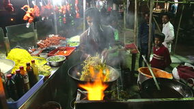 Indian man preparing local food at a street stand in night in Mumbai.