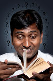 Indian man reading book. Curious Indian man reading book with many questions around his head stock images