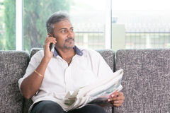 Indian man reading newspaper and calling phone Royalty Free Stock Photos