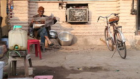 Indian man reading newspaper outside a house, with bike standing aside. stock footage