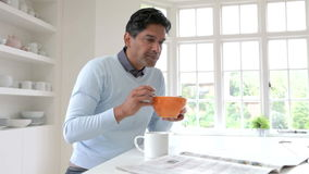 Indian Man Reading Newspaper Whilst Eating Breakfast stock video