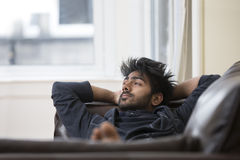 Indian man relaxing at home on the sofa. Royalty Free Stock Photography