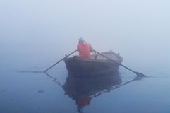 Indian man sailing on the boat on sacred river Ganges at cold foggy winter morning Stock Photo