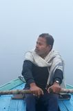 Indian man sailing on the boat on sacred river Ganges at cold foggy winter morning Stock Image
