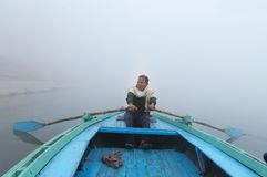 Indian man sailing on the boat on sacred river Ganges at cold foggy winter morning Royalty Free Stock Photos