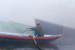 Indian man sailing on the boat on sacred river Ganges at cold foggy winter morning Stock Images