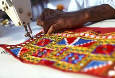Indian man sawing a textured fabric Royalty Free Stock Photography