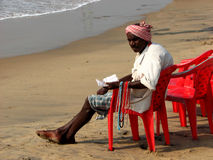Indian man selling necklaces. An Indian man selling necklaces on the beach, sitting in red plastic chair, waiting for customers in Puri, Orissa, India Royalty Free Stock Images