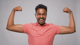 Indian man showing biceps over grey background. Power, strength, sport and people concept - happy young indian man showing biceps over grey background stock video footage