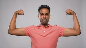 Indian man showing biceps over grey background. Power, strength, sport and success concept - happy young indian man showing biceps and celebrating success over stock video