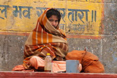 Indian man sits on the steps of ghat near sacred river Ganges in Varanasi Royalty Free Stock Image