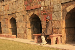 Indian man sitting on a bench at Mausoleum of Ghiyath al-Din Tug Royalty Free Stock Images