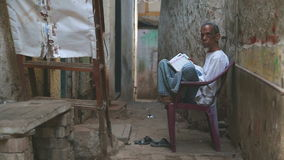 Indian man sitting on a chair and reading newspaper. stock footage