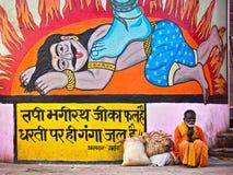 Indian Man Sitting By Colorful Hindu Art in Varanasi, India Royalty Free Stock Images