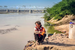 Indian Man sitting by the river Agra after he did laundry in t Stock Images