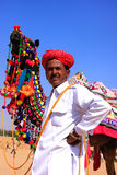 Indian man standing with his decorated camel at Desert Festival, Stock Images