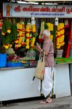Indian man stands at Little India flower garland shop Singapore. Singapore - August 4, 2015: An elderly white haired Indian man in traditional dhoti and shirt royalty free stock photography