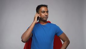 Indian man in superhero cape calling on smartphone stock video footage