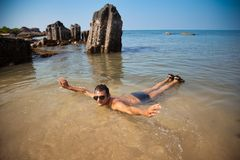 Indian man swimming at ocean beach Royalty Free Stock Photography