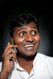 Indian man talking on the phone. Happy Indian man talking on the cell phone at black background Royalty Free Stock Photo
