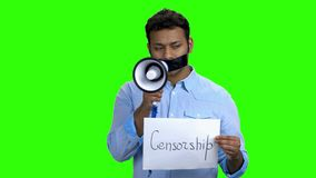 Indian man with taped mouth holding megaphone. Taped mouth man can not speak. Censorship in expression of opinion stock footage