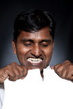 Indian man tearing paper sheet. Angry Indian man tearing white blank paper sheet with free space for text royalty free stock photography