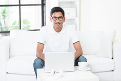 Indian man using computer at home. Royalty Free Stock Photos