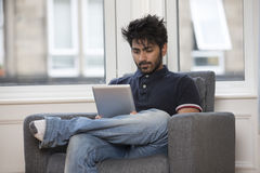 Indian man using digital tablet at home. Royalty Free Stock Photography