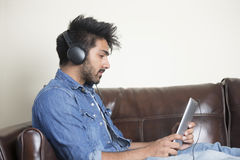 Indian man using digital tablet at home. Royalty Free Stock Photos