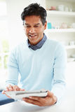Indian Man Using Digital Tablet At Home Royalty Free Stock Photo