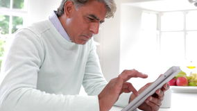Indian Man Using Digital Tablet In Kitchen At Home stock footage