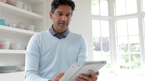 Indian Man Using Digital Tablet In Kitchen At Home stock video footage