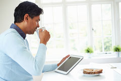 Indian Man Using Digital Tablet Whilst Eating Breakfast Stock Photos