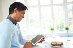 Indian Man Using Digital Tablet Whilst Eating Breakfast Royalty Free Stock Photos