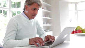 Indian Man Using Laptop Computer In Kitchen At Home stock footage