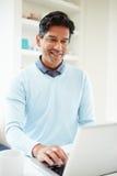 Indian Man Using Laptop At Home Stock Photo